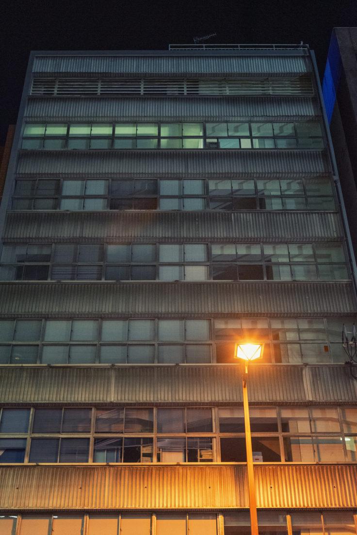 夜のビルを見上げる